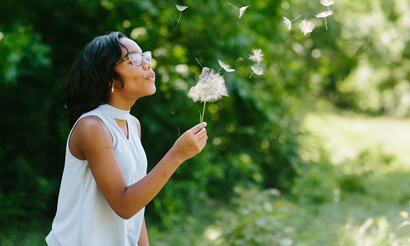 Jasmin making a wish on a dandelion and blowing the seeds into the wind
