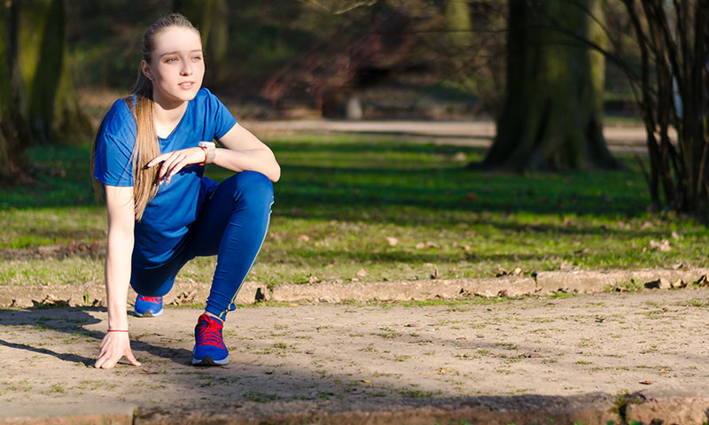 Teenage girl stretching before a run