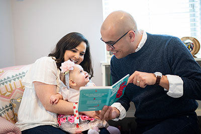 Olivia with her parents reading a book