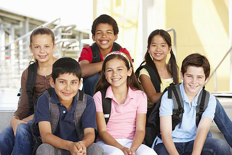 group of diverse kids sitting on school steps together