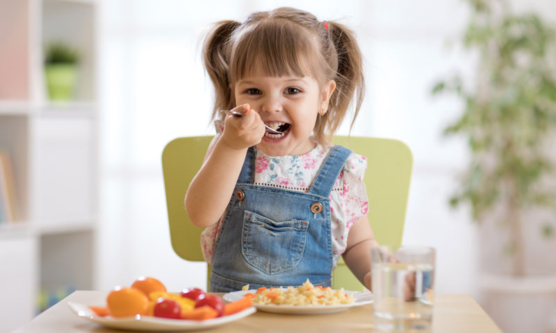 Little girl eating healthy foods at the table