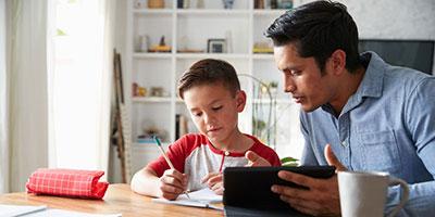 un hombre ayudando a un niño con las tareas escolares