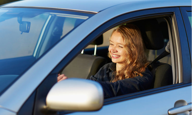confident young teenage girl driving a car