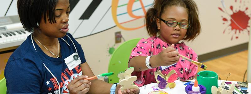 Ashlyn y su mamá se divierten en la sala de artes terapéuticas de Children's Health.