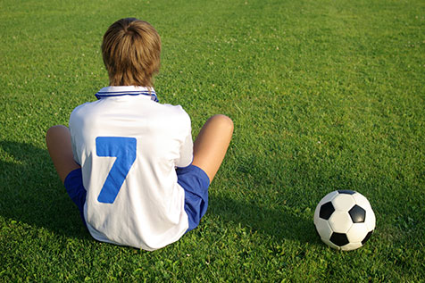 boy sitting on soccer field