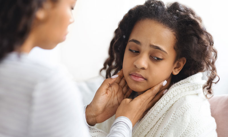 Little girl blowing nose while holding her teddy bear