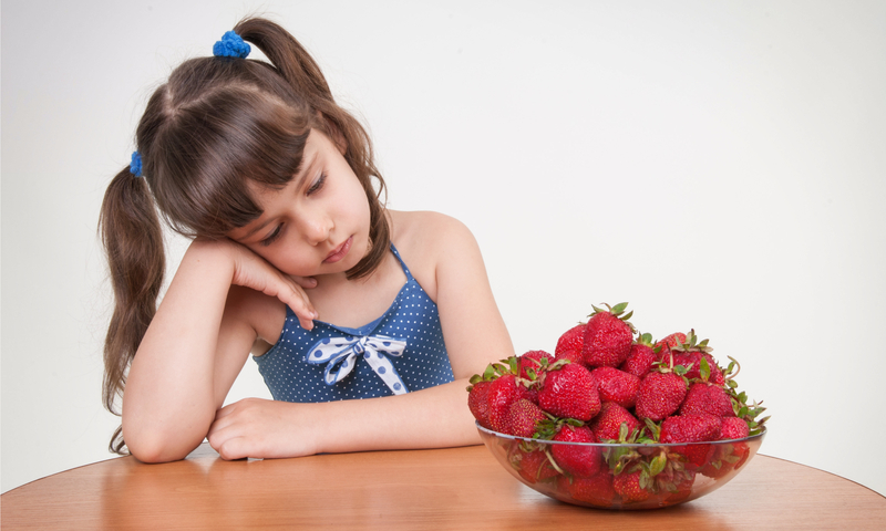 Little girl sitting at a table looking at bowl of strawberries