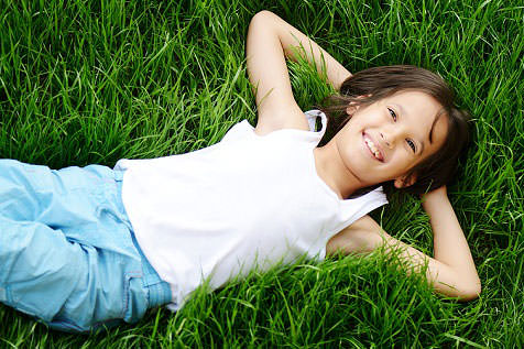 little girl laying back in grass