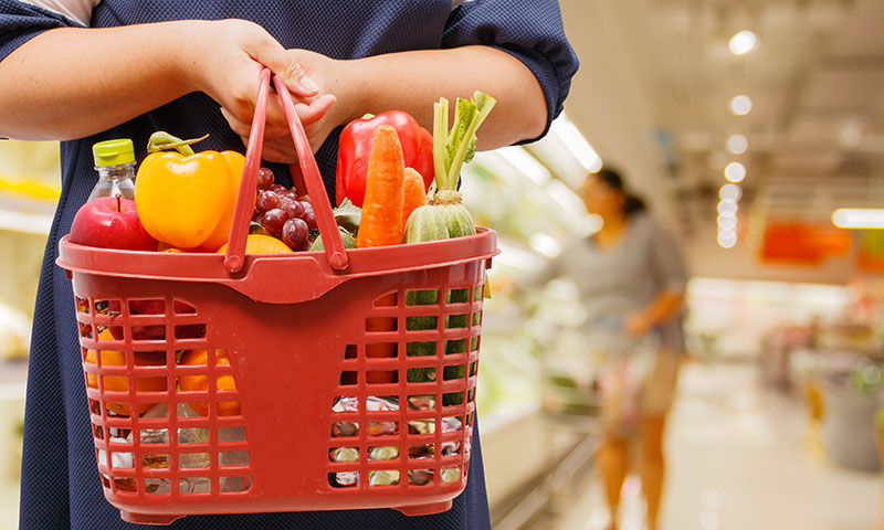woman holding shopping basket full of healthy foods