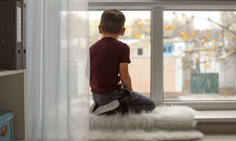 young boy sitting by the window looking outside