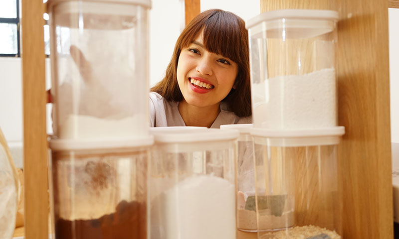 Asian woman looking for ingredients in pantry