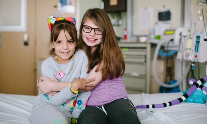Sisters hugging on hospital bed
