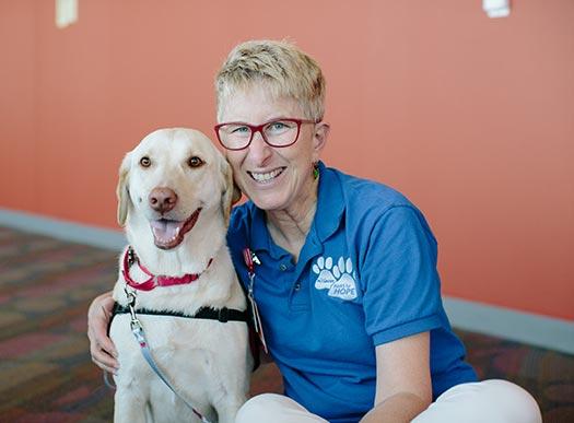 Voluntaria posando con un perro de servicios voluntarios
