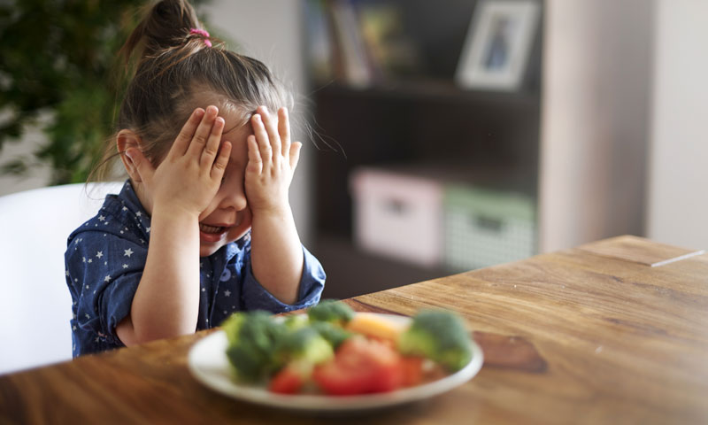 Little boy at store holding bell peppers