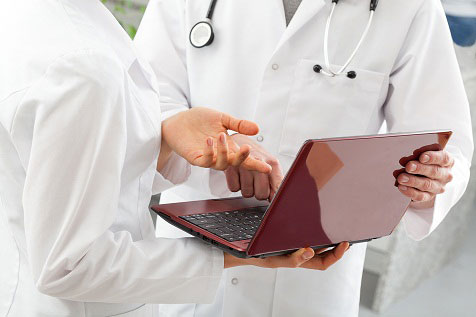 doctors holding laptop conferring