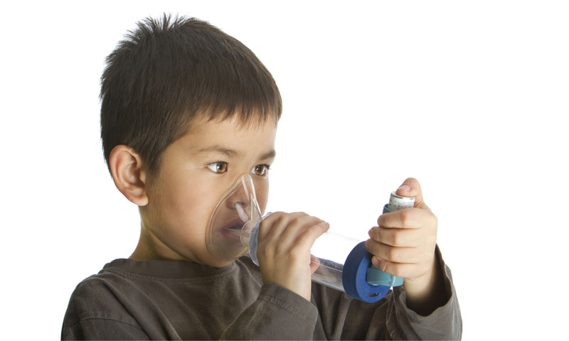 Young boy using his asthma inhaler