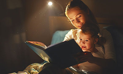 mother reading daughter bed time story