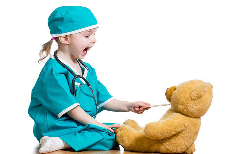 little girl dressed as surgeon using tongue depressor on teddy bear