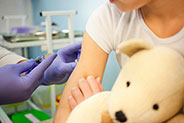 Little girl about to get a vaccine while holding teddy bear