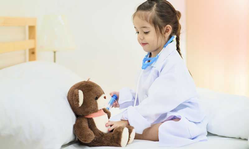 Little girl playing doctor giving her teddy bear a vaccine shot