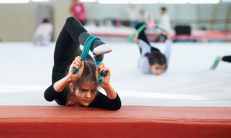 young gymnast stretches her back