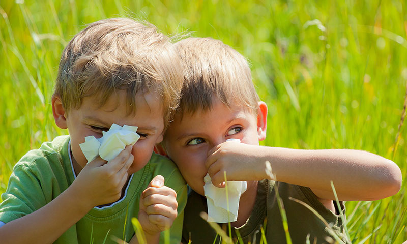 Two little boys blowing their noses outside