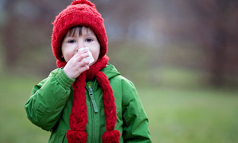 Boy outdoors blowing nose on winter day