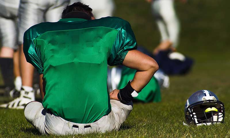 A tired football player is taking rest after the game