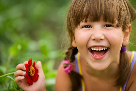 little girl with braided pig tails holing a red daisy