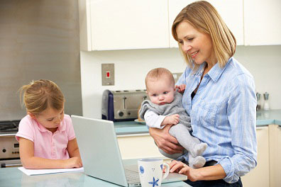 mother working on computer holding baby while other daughter colors