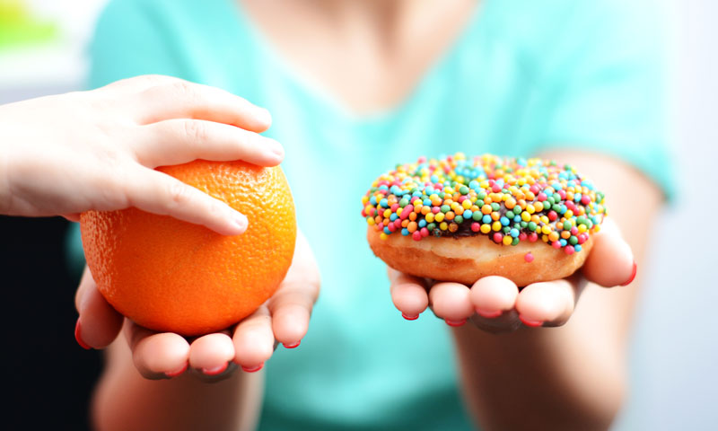 Mother holding an orange in one hand and a donut in the other, child's hand reaches to pick the orange