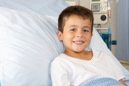 little boy smiling in hospital bed