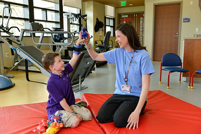 nurse helping young boy with physical therapy