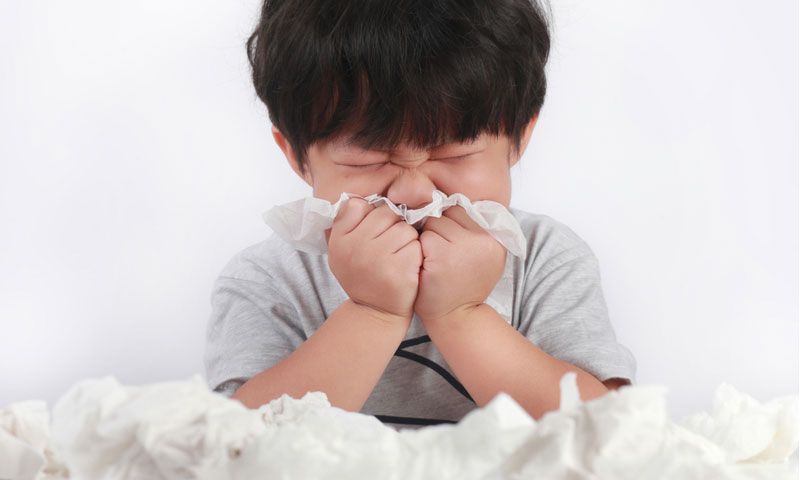 sick little boy wiping or cleaning nose with tissue