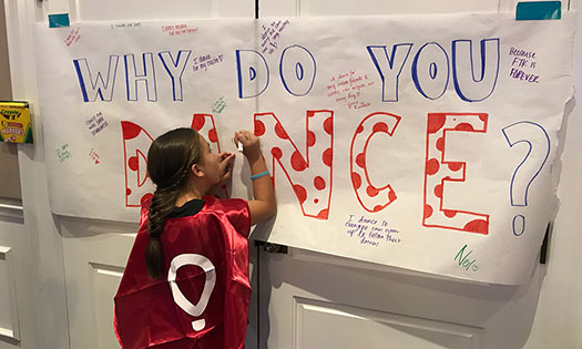 young girl signing a poster
