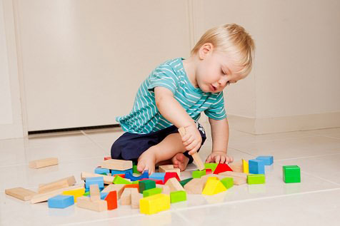 toddler playing with colorful blocks on the floor