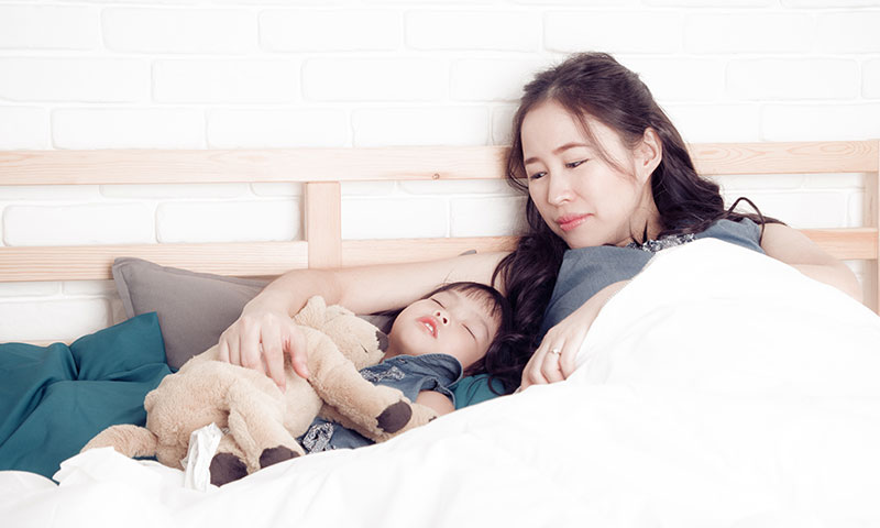 Asian mother watching over her sleeping child