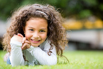 little girl on elbows in grass