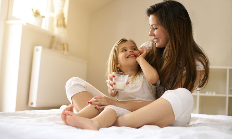 Mother holding daughter drinking milk on bed