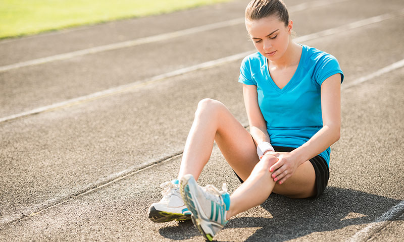 Teen girl sitting on a running track holding her knee