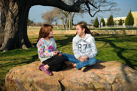 two little girls sitting on rock talking