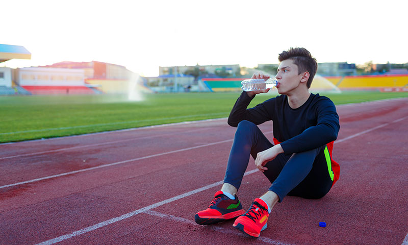 Teen athlete drinking water at running track