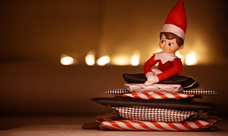 elf doll sitting on presents