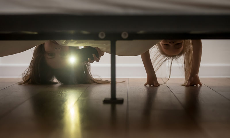 Mother and daughter checking under bed for monsters