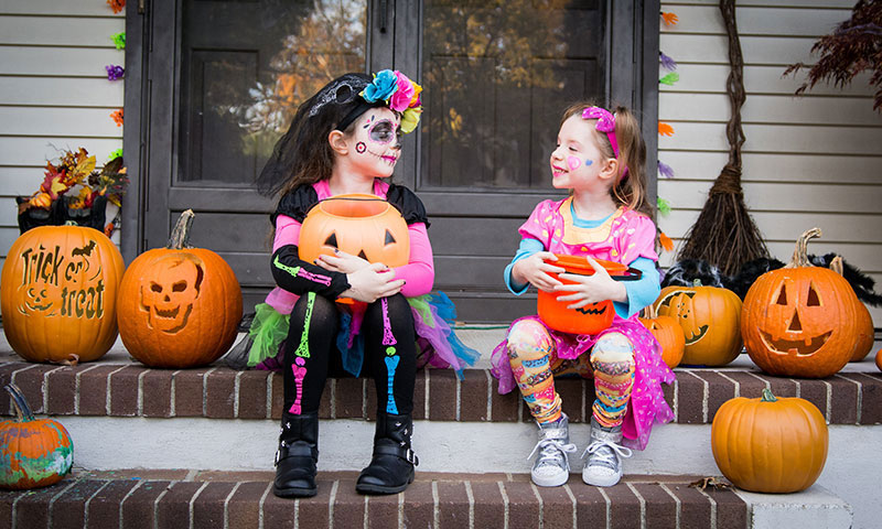 Children in Halloween costumes on front steps with pumpkins