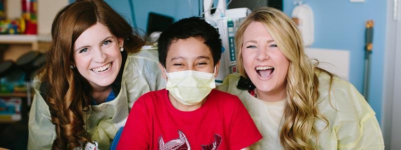 La especialista de vida infantil Katie Foley y Melissa Neely con su paciente Christian en la sala de juegos de Children's Health.