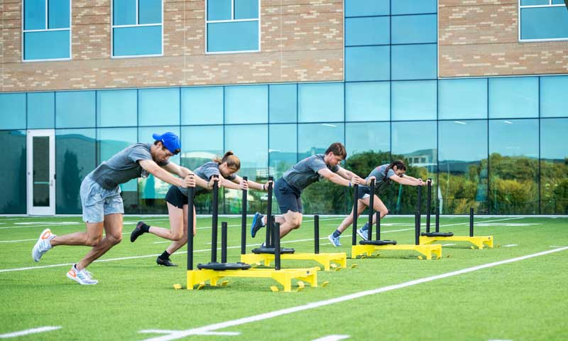 Teen boy and girl sitting on running track outside