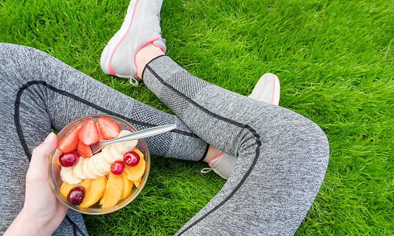 Young athlete sitting in the grass eating a bowl of colorful fruit