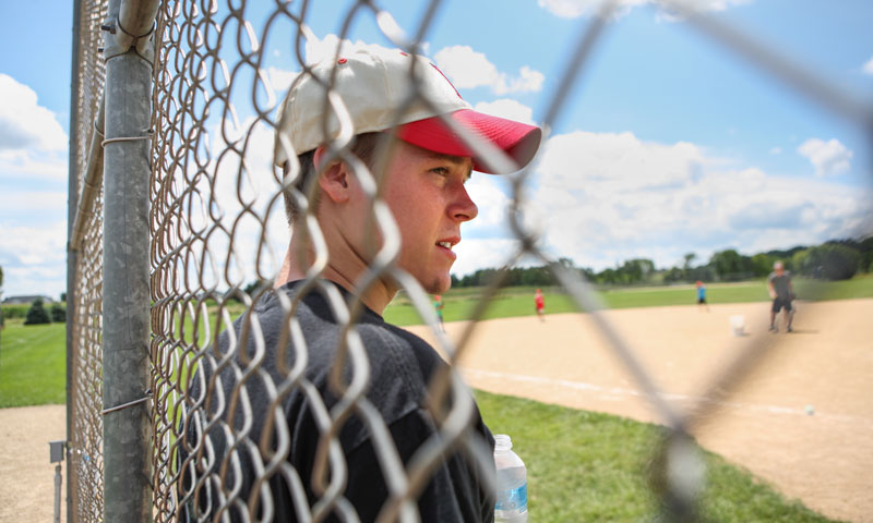 Injured baseball player watching game from sidelines