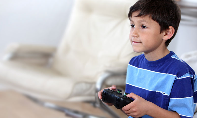 Little boy playing video game holding Xbox controller